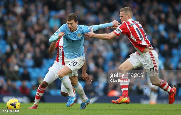 Edin Dzeko of Manchester City attempts to move away from Ryan Shawcross of Stoke City during the Barclays Premier League match between Manchester...