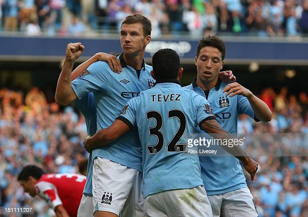 Edin Dzeko of Manchester City celebrates his goal with Carlos Tevez and Samir Nasri during the Barclays Premier League match between Manchester City...