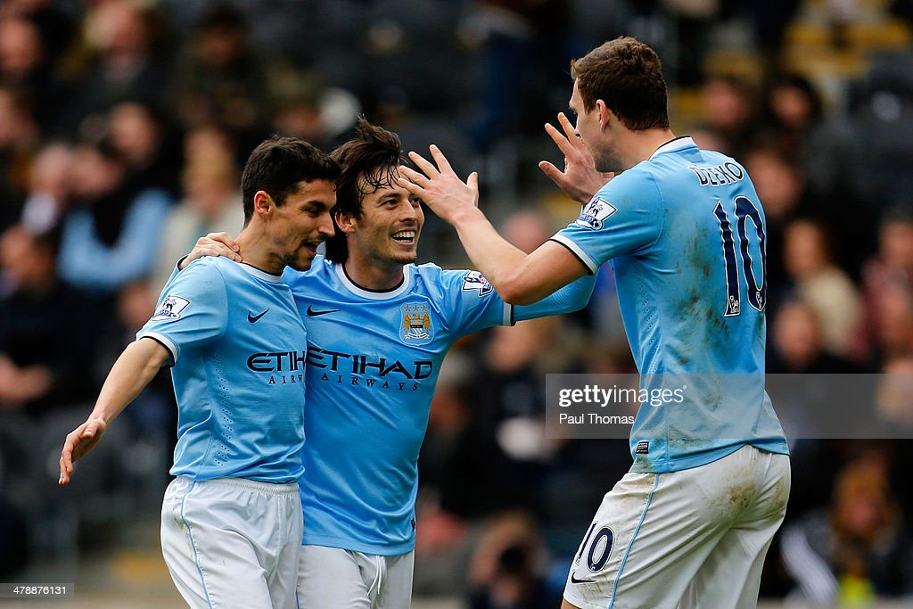 Edin Dzeko (R) of Manchester City celebrates his goal with team mates Jesus Navas (L) and David Silva during the Barclays Premier League match between Hull City and Manchester City at the KC Stadium on March 15, 2014 in Hull, England.