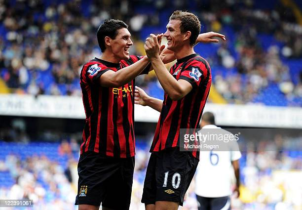 Edin Dzeko of Manchester City celebrates scoring his fourth goal with teammate Gareth Barry during the Barclays Premier League match between...