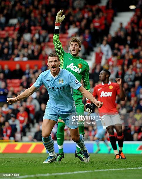 Edin Dzeko of Manchester City celebrates scoring his team's fourth goal during the Barclays Premier League match between Manchester United and...
