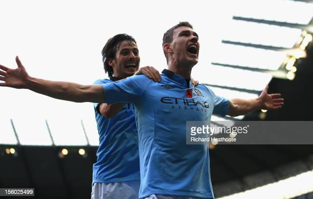 Edin Dzeko of Manchester City celebrates scoring his team's second goal with team-mate David Silva during the Barclays Premier League match between...