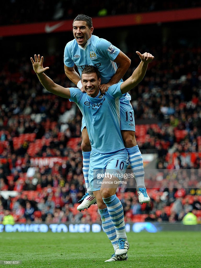 Edin Dzeko of Manchester City celebrates scoring his team's sixth goal with team mate Aleksandar Kolarov during the Barclays Premier League match between Manchester United and Manchester City at Old Trafford on October 23, 2011 in Manchester, England.