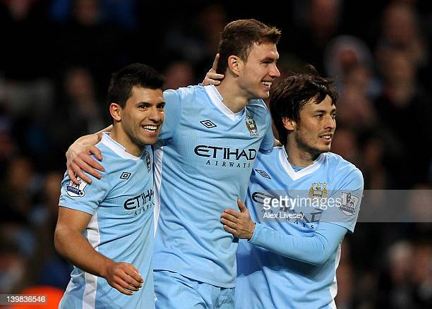 Edin Dzeko of Manchester City celebrates scoring his team's third goal with team mates Sergio Aguero and David Silva during the Barclays Premier...