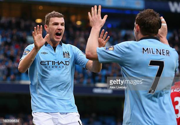Edin Dzeko of Manchester City celebrates scoring the opening goal with teammate James Milner during the Barclays Premier League match between...