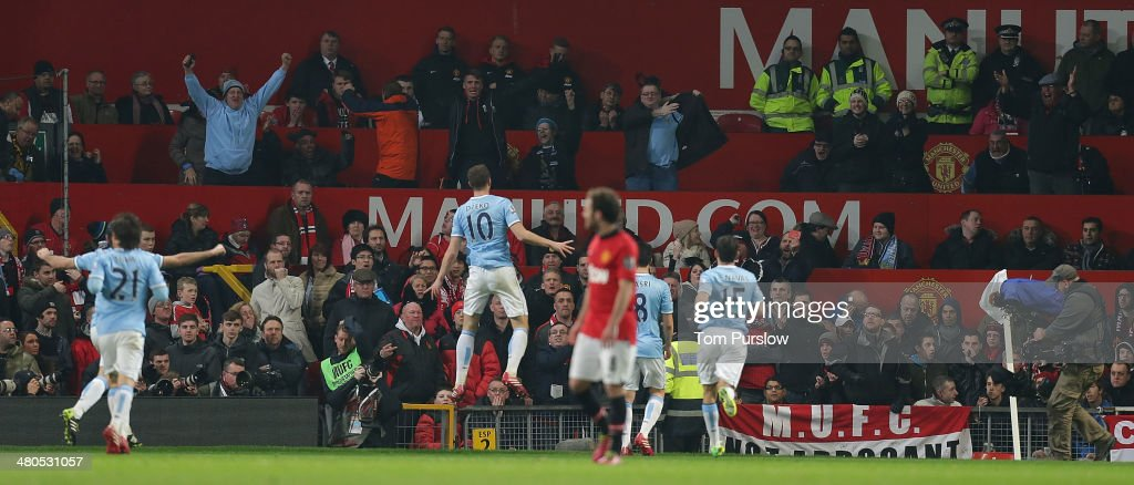 Edin Dzeko of Manchester City celebrates scoring their second goal during the Barclays Premier League match between Manchester United and Manchester City at Old Trafford on March 25, 2014 in Manchester, England.