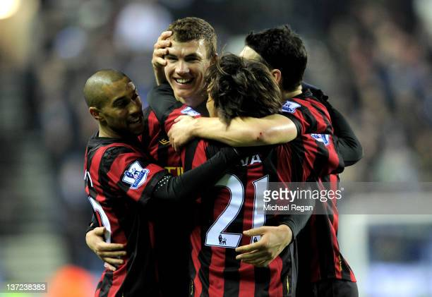 Edin Dzeko of Manchester City celebrates with his team mates after scoring the opening goal during the Barclays Premier League match between Wigan...