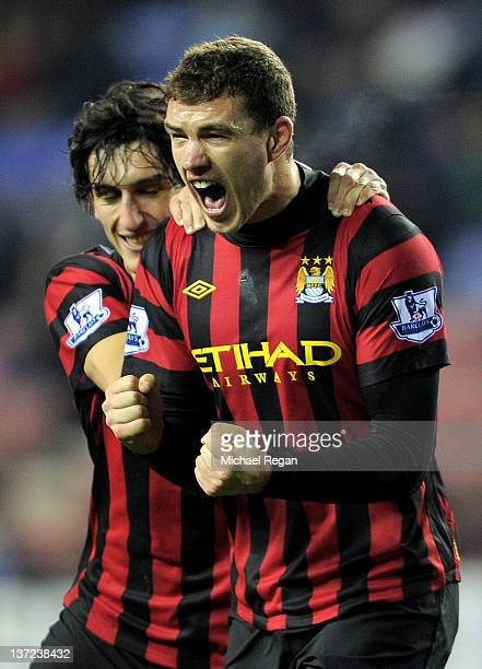 Edin Dzeko of Manchester City celebrates with team mate Stefan Savic after scoring the opening goal during the Barclays Premier League match between...