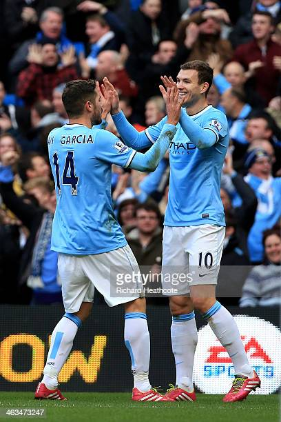 Edin Dzeko of Manchester City celebrates with teammate Javi Garcia after scoring the opening goal during the Barclays Premier League match between...