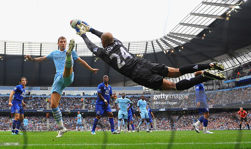 Edin Dzeko of Manchester City challenges as Tim Howard of Everton saves during the Barclays Premier League match between Manchester City and Everton at the Etihad Stadium on September 24, 2011 in Manchester, England.