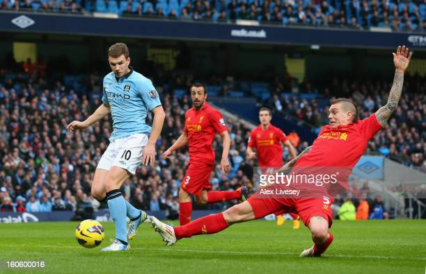 Edin Dzeko of Manchester City goes past the tackle of Daniel Agger of Liverpool to score the opening goal during the Barclays Premier League match...