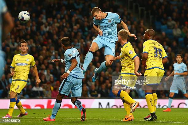 Edin Dzeko of Manchester City scores his sides fifth goal during the Capital One Cup Third Round match between Manchester City and Sheffield...
