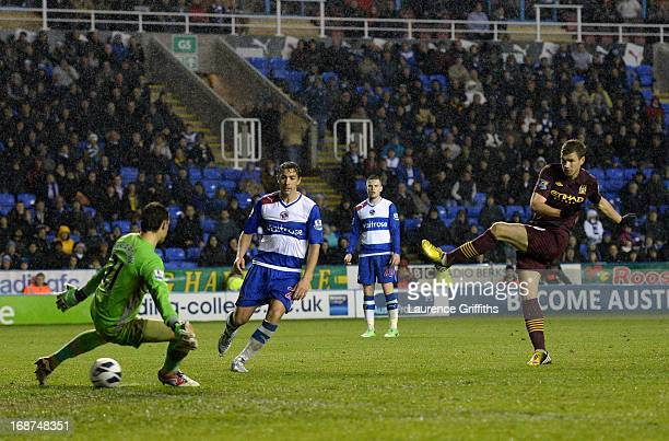 Edin Dzeko of Manchester City scores his sides second goal past Alex McCarthy of Reading during the Barclays Premier League match between Reading and...