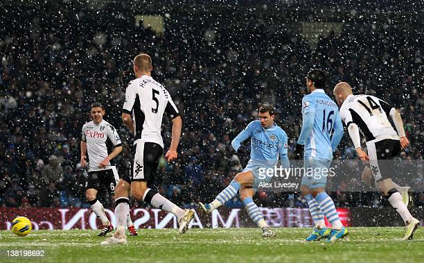 Edin Dzeko of Manchester City scores his team's third goal during the Barclays Premier League match between Manchester City and Fulham at the Etihad...
