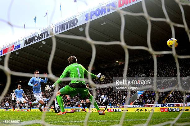 Edin Dzeko of Manchester City scores the opening goal past goalkeeper Tim Krul of Newcastle during the Barclays Premier League match between...
