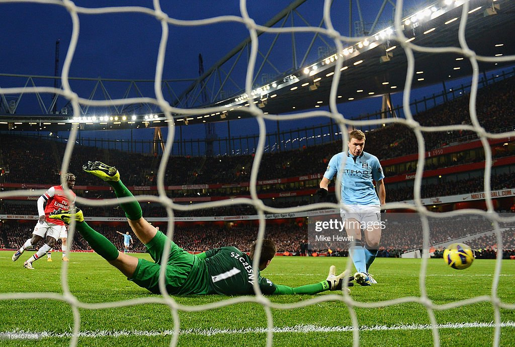 Edin Dzeko of Manchester City shoots past Wojciech Szczesny of Arsenal to score their second goal during the Barclays Premier League match between Arsenal and Manchester City at Emirates Stadium on January 13, 2013 in London, England.