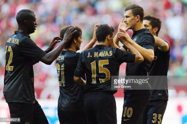 Edin Dzeko of Manchester scores his team's fourth goal with team mates during the Audi Cup match between Manchester City and AC Milan at Allianz...