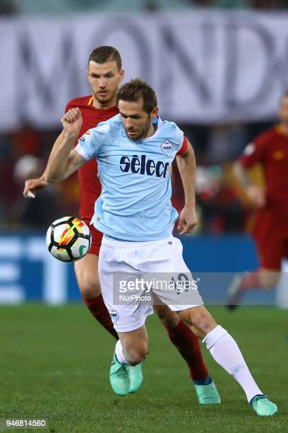 Edin Dzeko of Roma and Senad Lulic of Lazio during the serie A match between SS Lazio and AS Roma at Stadio Olimpico on April 15 2018 in Rome Italy