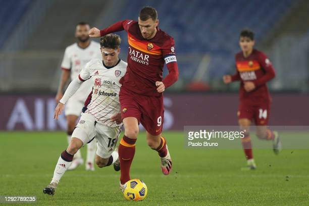 Edin Dzeko of Roma is challenged by Nahitan Nandez of Cagliari during the Serie A match between AS Roma and Cagliari Calcio at Stadio Olimpico on...