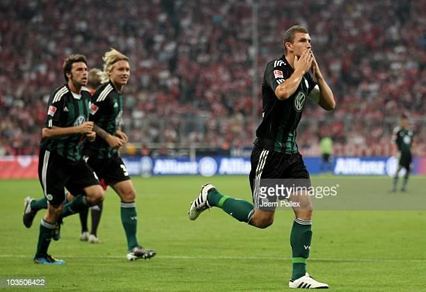 Edin Dzeko of Wolfsburg celebrates after scoring his team's first goal during the Bundesliga match between FC Bayern Muenchen and VfL Wolfsburg at...