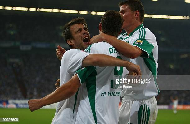 Edin Dzeko of Wolfsburg celebrates with team mates Alexander Madlung and Zvjezdan Misimovic after scoring the opening goal of Wolfsburg during the...