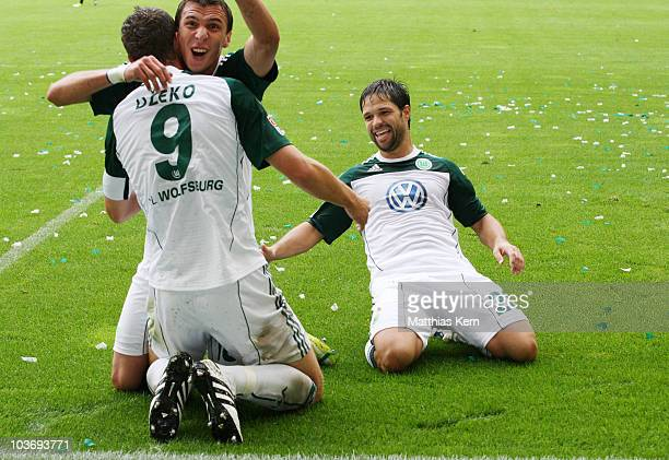 Edin Dzeko of Wolfsburg jubilates with Mario Mandzukic and Diego Ribas da Cunha after scoring the first goal during the Bundesliga match between VFL...