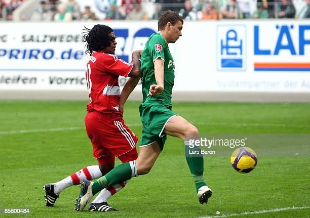 Edin Dzeko of Wolfsburg scores his team's second goal next to Breno of Muenchen during the Bundesliga match between VfL Wolfsburg and FC Bayern...