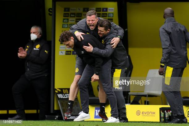 Edin Terzic, Head Coach of Borussia Dortmund and his backroom staff celebrate following their team's victory in the Bundesliga match between Borussia...