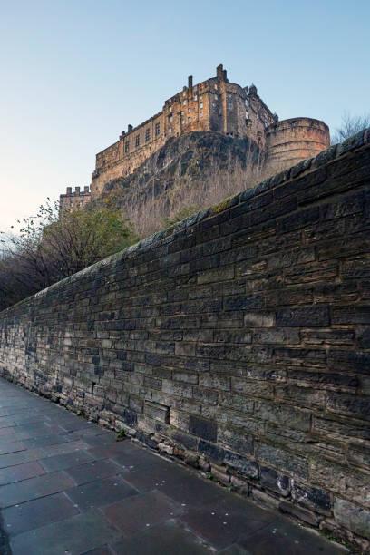Edinburgh Castle above brick wall at dusk