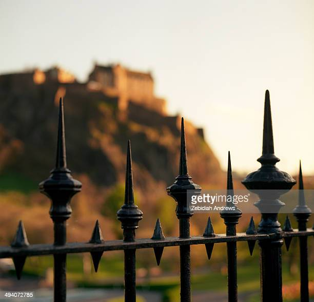 Edinburgh Castle in Scotland can be seen during golden hour as an out of focus background with the sharp points of a spiked metal fence providing...
