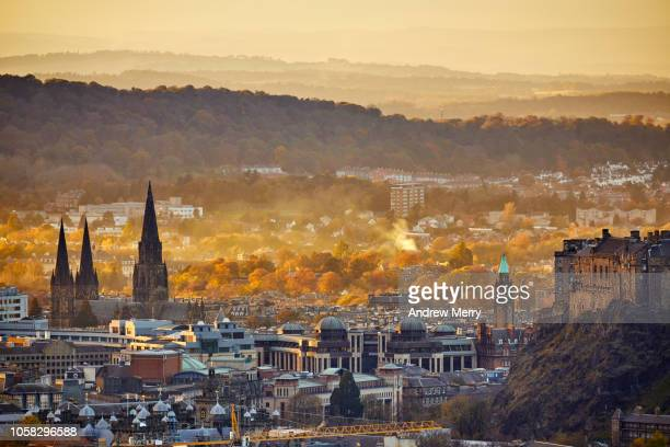edinburgh cityscape and mountains on skyline with st mary's cathedral steeples and autumn trees - edinburgh scotland stock pictures, royalty-free photos & images