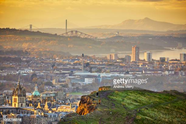 edinburgh cityscape and skyline with firth of forth at sunset from holyrood park - edinburgh schotland stockfoto's en -beelden