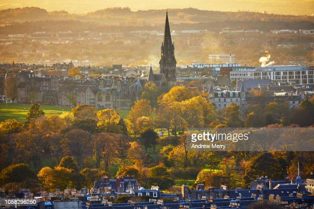 edinburgh cityscape with the meadows and the barclay viewforth church spire at sunset from salisbury crags, holyrood park - edinburgh scotland stock photos and pictures