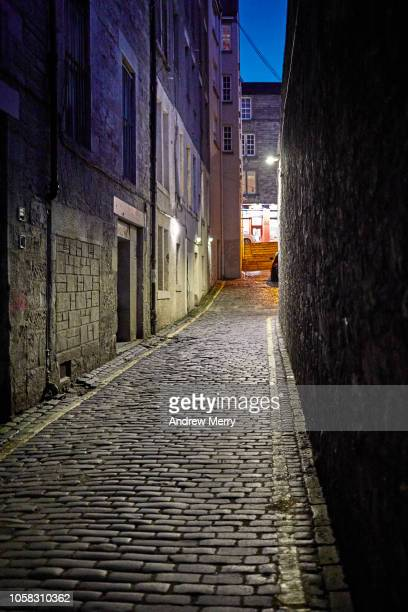Edinburgh Old Town cobblestone narrow alley, street at night with light at end with dark blue sky