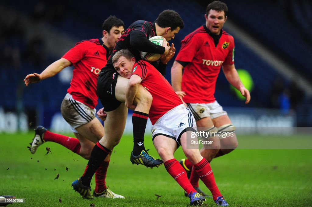 Edinburgh player Matt Scott is tackled by the Munster centre Keith Earls during the Heineken Cup Round 5 match between Edinburgh and Munster at Murrayfield Stadium on January 13, 2013 in Edinburgh, Scotland.