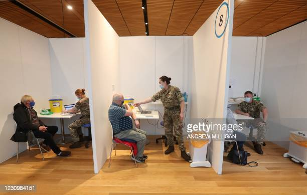 Edinburgh residents, Michael Maddocks and James Logan receive a Covid-19 vaccine from military personel at a temporary vaccination centre set up at...