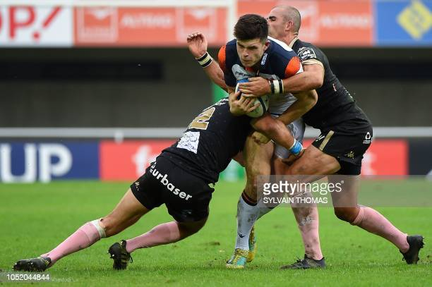 Edinburgh Rugby's Scottish fullback Blair Kinghorn is tackled by Montpellier's South African center Jan Serfontein and Montpellier's South African...