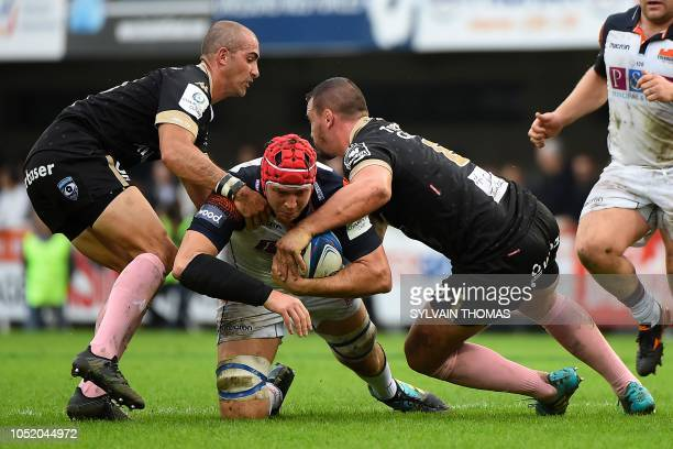 Edinburgh Rugby's Scottish lock Grant Gilchrist is tackled by Montpellier's French flanker Louis Picamoles and Montpellier's South African center...