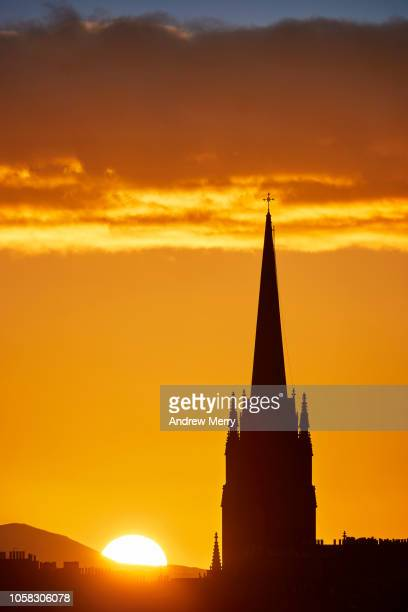 edinburgh skyline with close up of church steeple silhouette and setting sun on the horizon with illuminated clouds - 尖り屋根 ストックフォトと画像