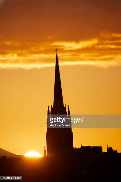 edinburgh skyline with close up of church steeple silhouette and setting sun on the horizon with illuminated clouds - aguja chapitel fotografías e imágenes de stock