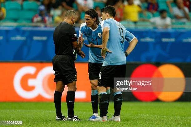 Edinson Cavani and Luis Suarez of Uruguay talk with referee Raphael Claus after the Copa America Brazil 2019 quarterfinal match between Uruguay and...