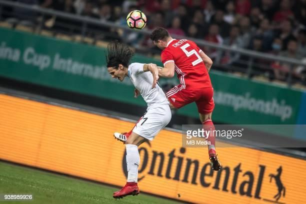 Edinson Cavani left of Uruguay national football team heads the ball to make a pass against James Chester of Wales national football team in their...