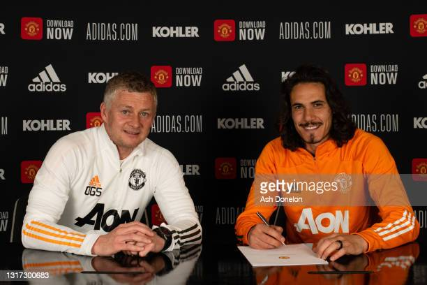 Edinson Cavani of Manchester United poses with Manager Ole Gunnar Solskjaer after signing a contract extension at Aon Training Complex on May 10,...