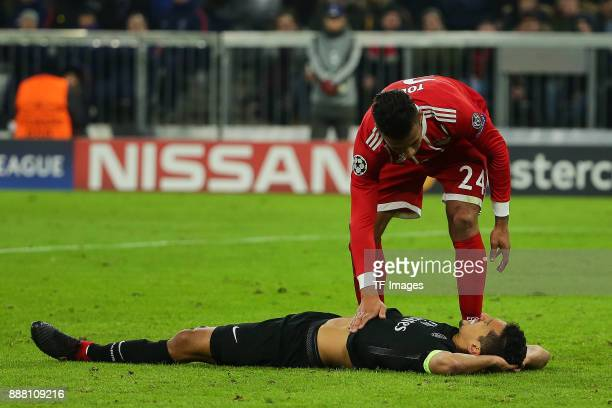 Edinson Cavani of Paris SaintGermain lays injured on the ground and Corentin Tolisso of Bayern Muenchen helps during the UEFA Champions League group...
