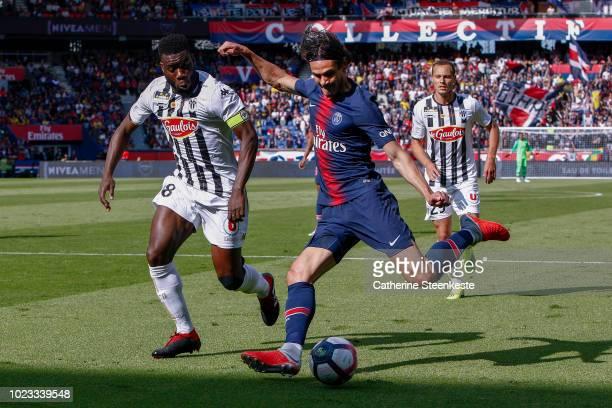 Edinson Cavani of Paris SaintGermain shoots the ball against Ismael Traore of Angers SCO during the Ligue 1 Conforama game between Paris SaintGermain...