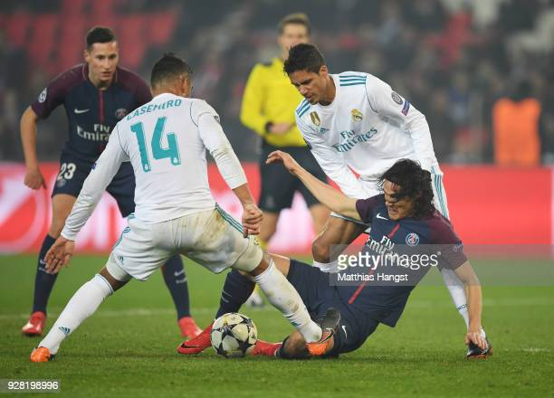 Edinson Cavani of PSG tangles with Casemiro and Raphael Varane of Real Madrid during the UEFA Champions League Round of 16 Second Leg match between...