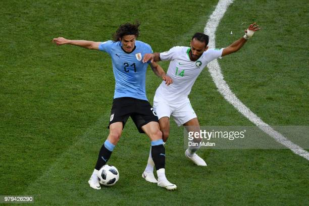 Edinson Cavani of Uruguay battles for possession with Abdullah Otayf of Saudi Arabia during the 2018 FIFA World Cup Russia group A match between...