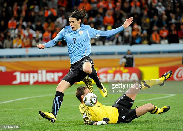 Edinson Cavani of Uruguay jumps over goalkeeper Maarten Stekelenburg of the Netherlands during the 2010 FIFA World Cup South Africa Semi Final match...