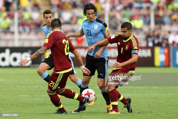 Edinson Cavani of Uruguay tries to dribble Tomas Rincon and Junior Moreno of Venezuela during a match between Venezuela and Uruguay as part of FIFA...