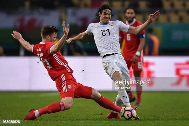 Edinson Cavani right of Uruguay national football team kicks the ball to make a pass against Lee Evans of Wales national football team in their final...
